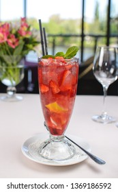 cocktail with strawberries, mint and ice in a glass tumbler