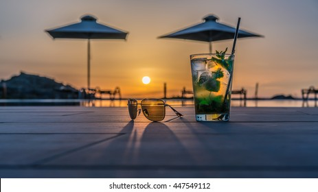 Cocktail with sunglasses near the swimming pool