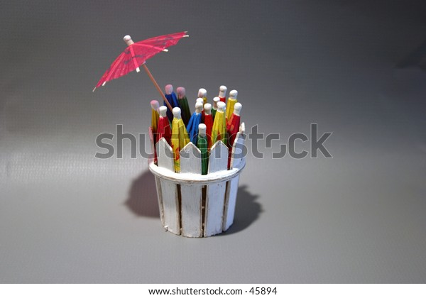 cocktail umbrellas of diffrent colors folded up sit in a white picket basket on a gray background with a pink open umbrella