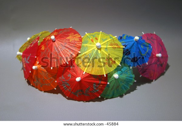 cocktail umbrellas of diffrent colors sit on a gray background