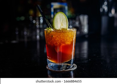 A cocktail with whiskey or cognac or Cola in a highball glass is on the counter of a dark bar.