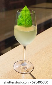 Cocktail in a Wine Glass with a Bright Green Basil Leaf