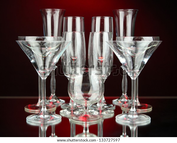 Cocktail and wine glasses, on dark red background
