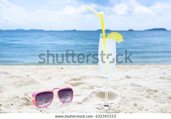 cocktail,lemonade and pink glasses on sea background