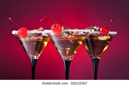 cocktails with cherry and ice on red background