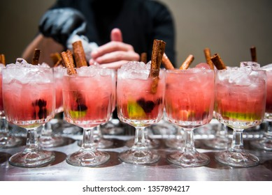 Cocktails with cinnamon sticks served during a party.