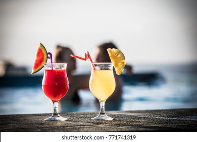 Cocktails and the couple in swimming pool