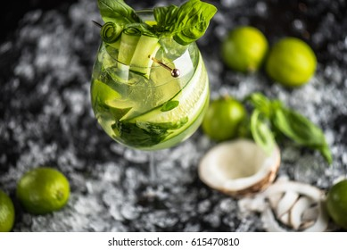 Cocktails in a glass, coconut, lime, cucumber on ice on a dark background. A drink of fresh lemonade close-up.