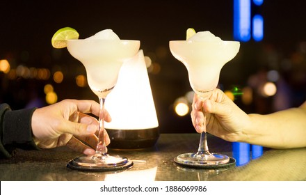 Cocktails with hand holding of husband and wife on Valentine's day romantic dinner in restuarant with night light background.
