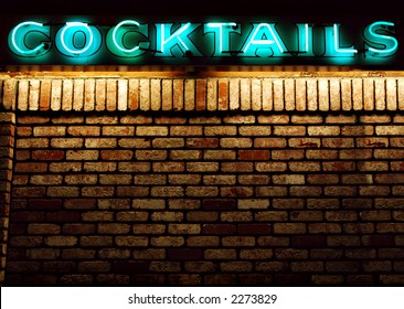 Cocktails neon sign above an old brick wall with copyspace available