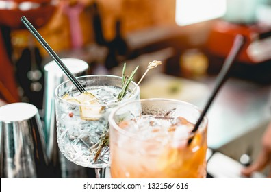 Cocktails served on bar counter prepared with gin, rosemary, paper and orange juice - Drink, nightlife, lifestyle concept - Focus on top crystal glass
