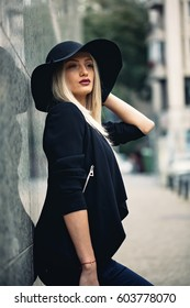 Cocky blonde bimbo, posing beside grey wall, having arrogant look on face, standing with her mouth ajar. Holding hand on black floppy hat that matches her black flared jacket and black outfit.