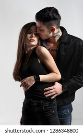 Cocky guy in black jacket on a naked torso is hugging from behind a brunette girl dressed in a black t-shirt and jeans in a studio on the white background. Young and cocky lovers