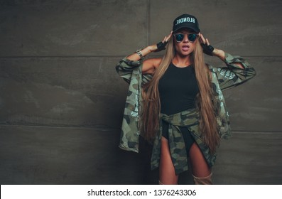 Cocky sexy fashion woman with long hair posing on studio dressed in bodysuit and black cap