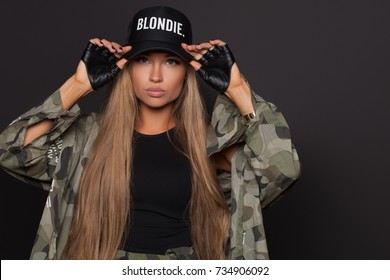 Cocky sexy fashion woman with long hair posing on studio dressed in bodysuit and black cap isolated on black