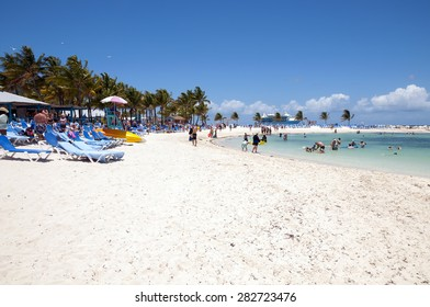COCO CAY, BAHAMAS - MAY 26, 2015: Sandy beach with people enjoying sun and fun with their Royal Caribbean cruise ship anchored in the background