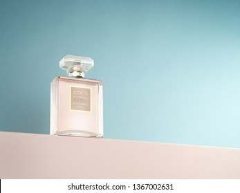 Coco Mademoiselle Chanel Paris perfume. This product photography of softly lit perfume on light blue background and pink base is a professional product photo.