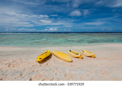 Coco Palm Garden Beach in Guam, USA. There are yellow sea kayaks on the beach contiguous to the coral reef with transparent water.