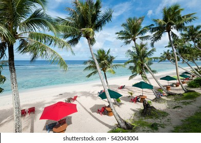 Coco Palm Garden Beach in Guam, USA. There are beach umbrellas, chairs on the white sand and palm trees on the beach contiguous to the coral reef with transparent water.