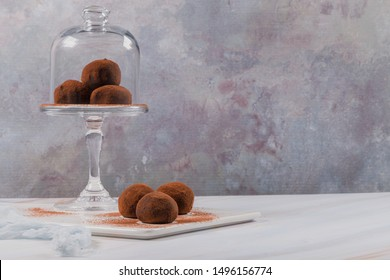 Cocoa balls, chocolate balls cakes in a glass stand, sprinkled with cocoa powder.