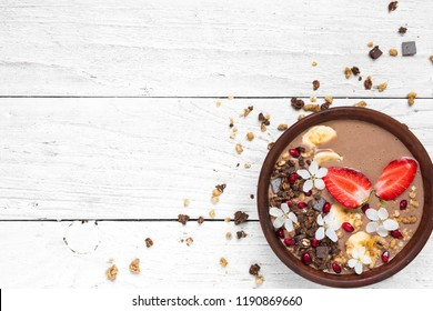 cocoa banana protein smoothie bowl with chocolate granola, strawberry and pomegranate seeds decorated with flowers. top view with copy space. healthy breakfast