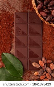 Cocoa beans in pod, theobroma cacao leafes and  chocolate bar flat lay on table. Delicious dark chocolate background.