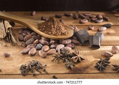 cocoa beans, powder, cinnamon, star anise and cloves with wooden bottom