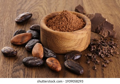 Cocoa beans, powder, crushed cocoa beans and chocolate on wooden background.