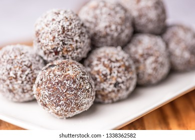Cocoa Berry Protein Balls are stacked up on a diagonal white plate