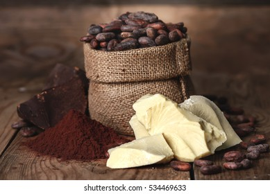 Cocoa butter and ingredients for making chocolate, Cocoa powder in the bowl, cocoa beans on old wooden background