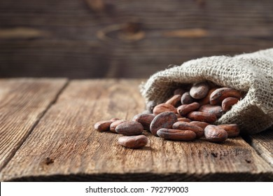 Cocoa (cacao) beans in sackcloth bag on a wooden table.