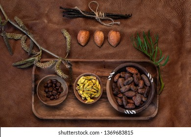 Cocoa, cardamom, coffee beans, almonds and vanilla on natural background.