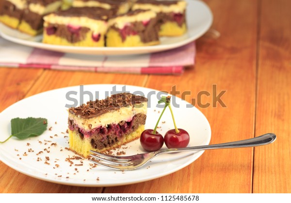 """Cocoa cherry cake, called """"Danube Wave"""". Top with vanilla cream and chocolate. A plate with a slice of cake at the wooden table."""