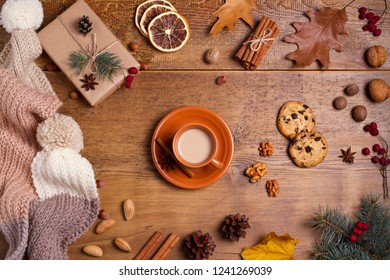 Cocoa, coffee, gift box, fir branch, nuts, cones, cookies, knitted woolen scarf and hat. Winter, New Year, Christmas composition. Cosy autumn-winter concept. View from above