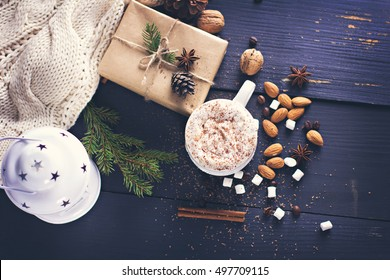 Cocoa, coffee  with marshmallows, fir branch, nuts, gift, cozy knitted blanket. Winter, New Year, Christmas still life.
