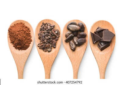 cocoa and dark chocolate in wooden spoons on white background