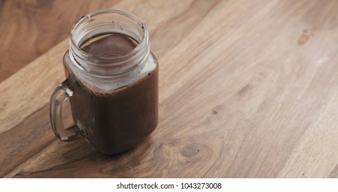 cocoa drink in glass jar with handle on wood table