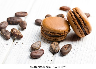 cocoa macaroons with cocoa beans on wooden table