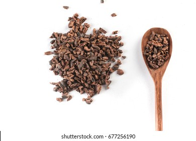 Cocoa Nibs into a spoon isolated on white background