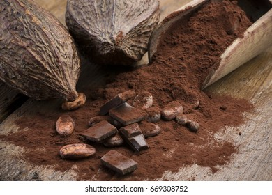 cocoa pods with cocoa beans, cocoa powder and chocolate block on wooden table