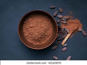 Cocoa powder in a bowl on the black background