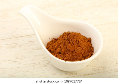 Cocoa powder in the bowl over the wooden background