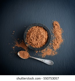 Cocoa powder in a bowl with spoon on the black slate background, top view