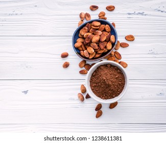 Cocoa powder and cacao beans on wooden background. Dark chocolate pieces crushed and aromatic herbs .