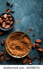 Cocoa powder and cacao beans on dark background, top view