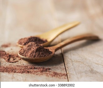 Cocoa powder on a spoon over a wooden table.