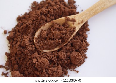Cocoa powder and a wooden spoon over a white background. It contains flavonoids with the function as antioxidants that help prevent systemic inflammation.