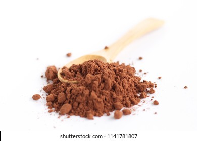 Cocoa powder with a wooden spoon over a white background. It contains flavonoids with the function as antioxidants that help prevent systemic inflammation.