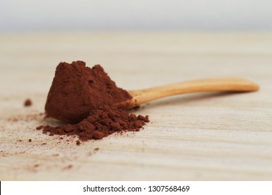 Cocoa powder and a wooden spoon over on the table. The subject contains flavonoids with the function as antioxidants that help prevent systemic inflammation.
