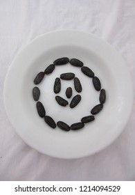 Cocoa seeds arranged round on white plate